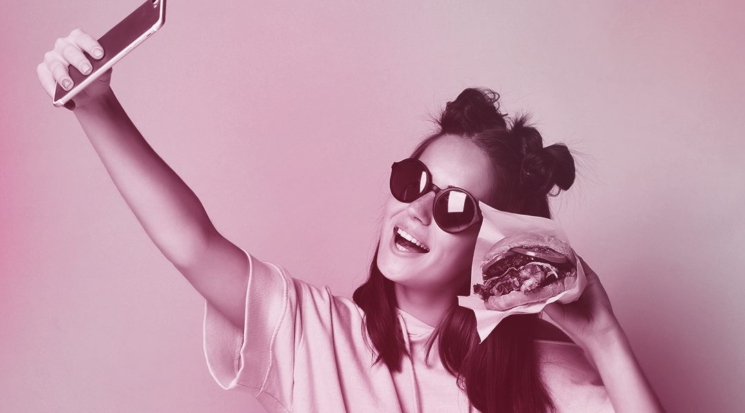 Woman posing with burger and taking selfie (Branding and Packaging)