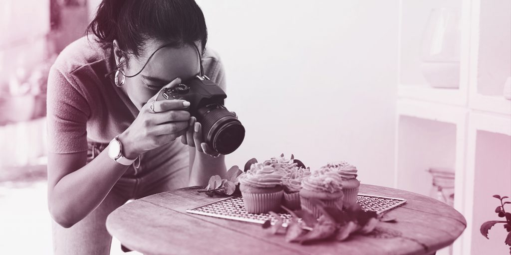 Woman holding a camera and taking a picture of cupcakes on a round table (Social Media Optimisation)