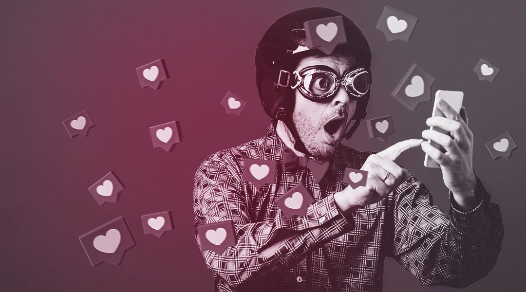 Man in helmet and goggles, holding a phone as heart symbols float around him (Social Media Optimisation)